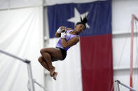 Reigning Olympic champion gymnast Simone Biles practices her routine on the uneven bars during a training session Tuesday, May 11, 2021, in Spring, Texas. (AP Photo/David J. Phillip)