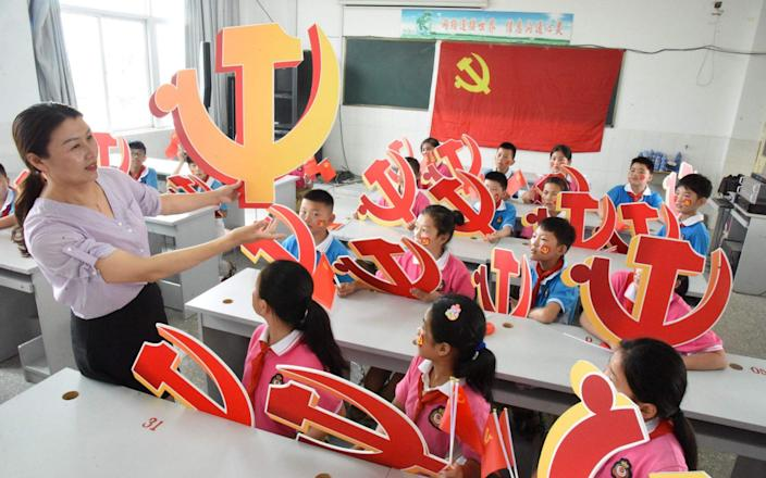 A teacher and her students pose with Communist Party emblems during a class about the history of the Communist Party at a school in Lianyungang, in China's eastern Jiangsu province - AFP