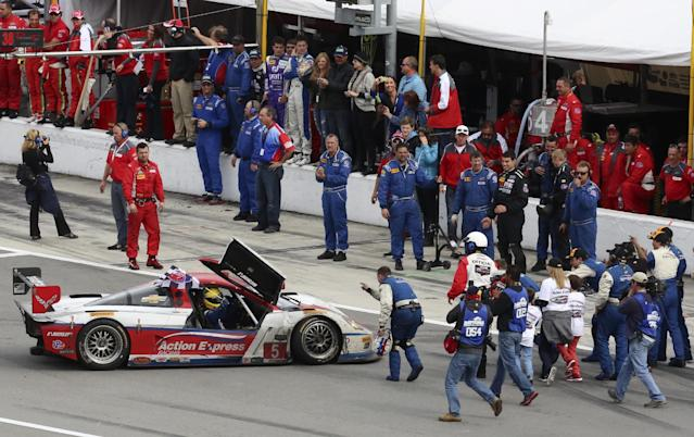 Driver Joao Barbosa, waves the checkered flag from his car as he is surrounded by crew members and photographers after winning the IMSA Series Rolex 24 hour auto race at Daytona International Speedway in Daytona Beach, Fla., Sunday, Jan. 26, 2014.(AP Photo/David Graham)