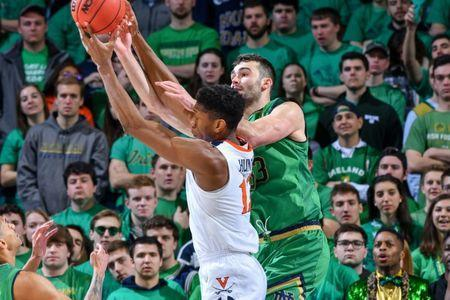 Jan 26, 2019; South Bend, IN, USA; Virginia Cavaliers guard De'Andre Hunter (12) and Notre Dame Fighting Irish forward John Mooney (33) reach for a rebound in the second half at the Purcell Pavilion. Mandatory Credit: Matt Cashore-USA TODAY Sports