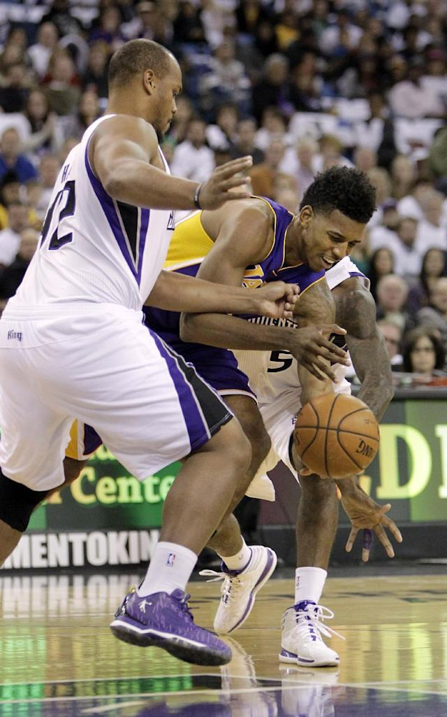 Los Angeles Lakers guard Nick Young, center, looses the ball as he tries to dribble between Sacramento Kings' Chuck Hayes, left, and John Salmons during the first quarter of an NBA basketball game in Sacramento, Calif., Friday, Dec. 6, 2013. (AP Photo/Rich Pedroncelli)