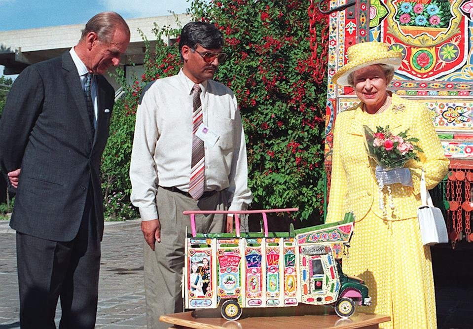 The Queen and Prince Philip view a model of a traditionally painted truck in the compound of the British High Commission in Pakistan. The Queen arrived on her second state visit to Pakistan as the country celebrated its 50th anniversary of independence from British colonial rule. (Photo by TANVEER MUGHAL/AFP via Getty Images)