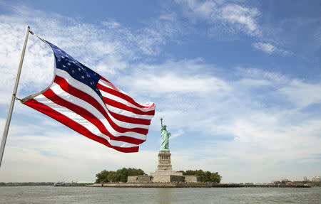An U.S. flag waves in the wind on a boat near the Statue of Liberty in New York