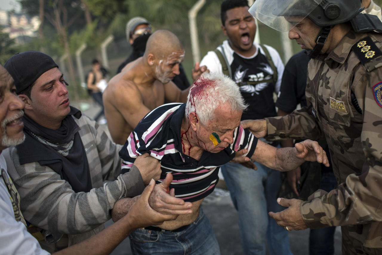 A man hit with a projectile fired by police during a protest is taken away by a military policeman and fellow demonstrators outside the Minerao stadium during a soccer Confederations Cup match between Japan and Mexico in Belo Horizonte, Brazil, Saturday, June 22, 2013. Thousands of anti-government demonstrators again took to streets in several Brazilian cities Saturday after the president broke a long silence to promise reforms.(AP Photo/Felipe Dana)