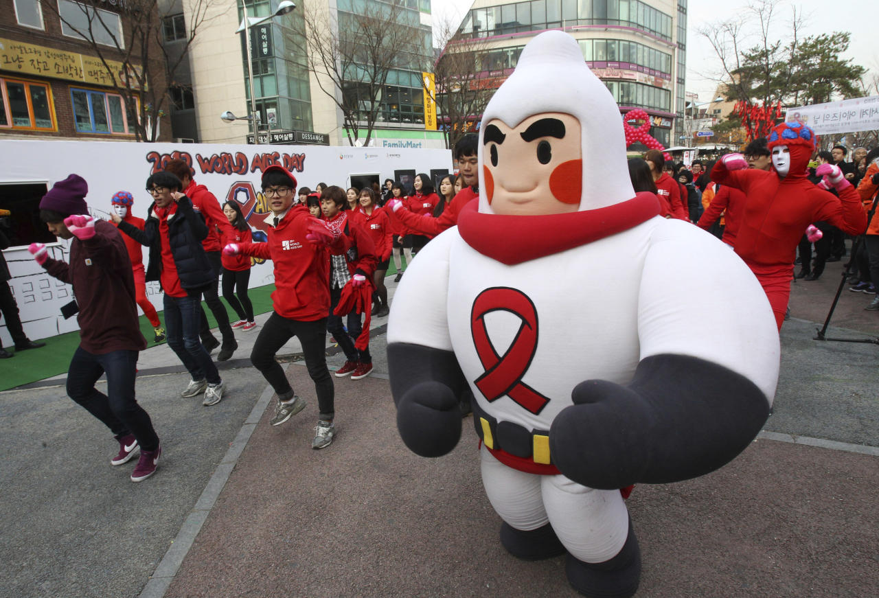 A volunteer wearing a costume featuring a condom performs with others during an AIDS awareness campaign in Seoul, South Korea, Friday, Nov. 30, 2012. World AIDS Day is observed on Dec. 1 to increase awareness about the disease. (AP Photo/Ahn Young-joon)