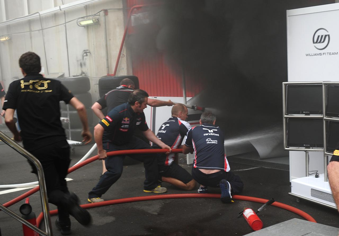 Racing team crews use a fire hose to try and extinguish a fire in the Williams racing pit stand at the Circuit de Catalunya on May , 2012 in Montmelo on the outskirts of Barcelona after the Spanish Formula One Grand Prix. AFP PHOTO / DIMITAR DILKOFFDIMITAR DILKOFF/AFP/GettyImages
