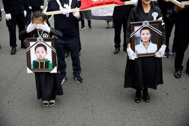 PHOTO: A girl and her North Korean defector mother hold portraits of a 42-year-old defector mother and her 6-year-old son who were found dead in starvation as they march during their funeral in Seoul, South Korea, Sept. 21, 2019. (Kim Hong-ji/Reuters, FILE)