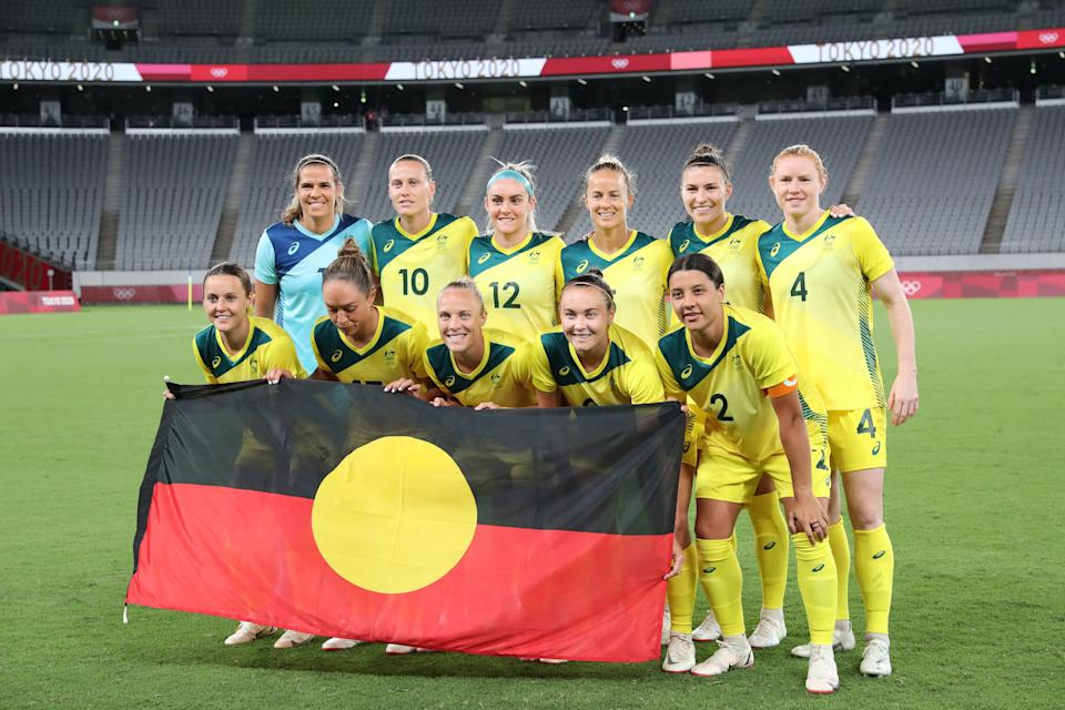 (From L, front) Australia's forward Hayley Raso, Australia's forward Kyah Simon, Australia's midfielder Tameka Yallop, Australia's forward Caitlin Foord, Australia's forward Sam Kerr and (From L, Rear) Australia's goalkeeper Lydia Williams, Australia's midfielder Emily van Egmond, Australia's defender Ellie Carpenter, Australia's midfielder Aivi Luik, Australia's defender Steph Catley and Australia's defender Clare Polkinghorne pose for a team photo with the Australian Aboriginal flag prior to the Tokyo 2020 Olympic Games women's group G first round football match between Australia and New Zealand at the Tokyo Stadium in Tokyo on July 21, 2021. (Photo by Yoshikazu TSUNO / AFP) (Photo by YOSHIKAZU TSUNO/AFP via Getty Images)