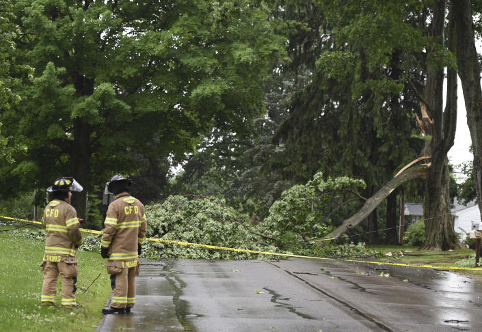 Concord firefighters work at the scene of a downed tree and power line on Main Street on Wednesday, June 10, 2020. Strong storms with heavy winds swept across Jackson County causing power outages, downing trees and damaging property. (J. Scott Park/Jackson Citizen Patriot via AP)