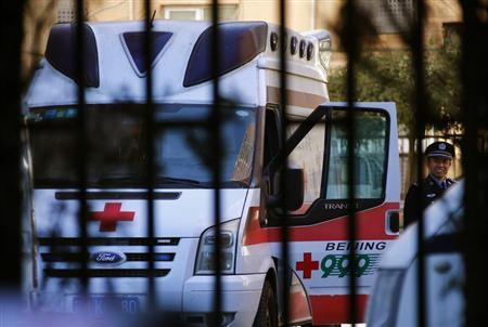 A policeman is seen through a fence as he stands beside an ambulance believed to be carrying Ji Zhongxing in Beijing