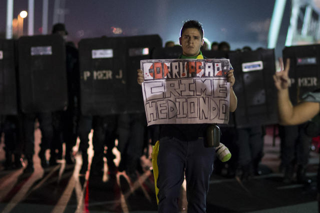 "A man holds a sign that reads in Portuguese; ""Corruption: Heinous crime,"" in front of an advancing group of military police dressed in riot gear, at an anti-government protest near the Cidade de Deus, or City of God slum in Rio de Janeiro, Brazil, Friday, June 21, 2013. City centers around Brazil were still smoldering on Friday after 1 million protesters took to the streets amid growing calls on social media for a general strike next week. While most protesters were peaceful, some small groups clashed violently with police, who responded in some cases with tear gas, pepper spray and rubber bullets. (AP Photo/Felipe Dana)"