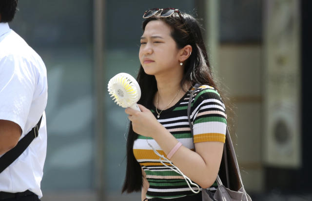 <p>A woman holds a portable fan at a business district in Tokyo, July 23, 2018. (Photo: Koji Sasahara/AP) </p>