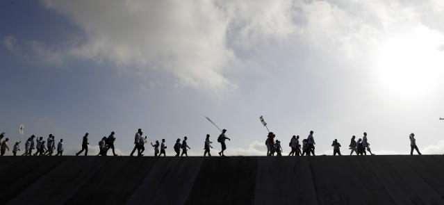 Hundreds of people march along a levee in South Texas toward the Rio Grande to oppose the wall the U.S. government wants to build on the river separating Texas and Mexico, Saturday, Aug. 12, 2017, in Mission, Texas. The area would be the target of new barrier construction under the Trump administration's current plan. (AP Photo/Eric Gay)