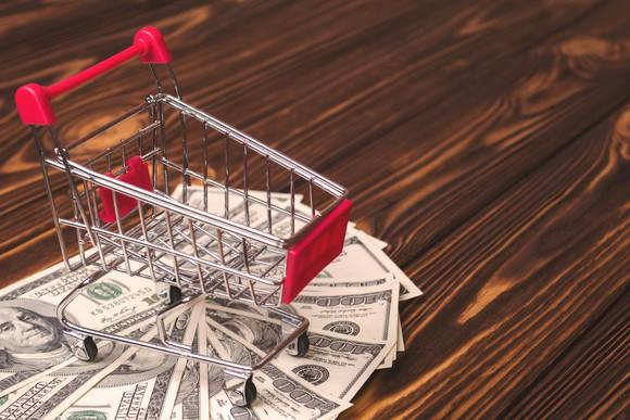 A shopping cart with cash underneath.