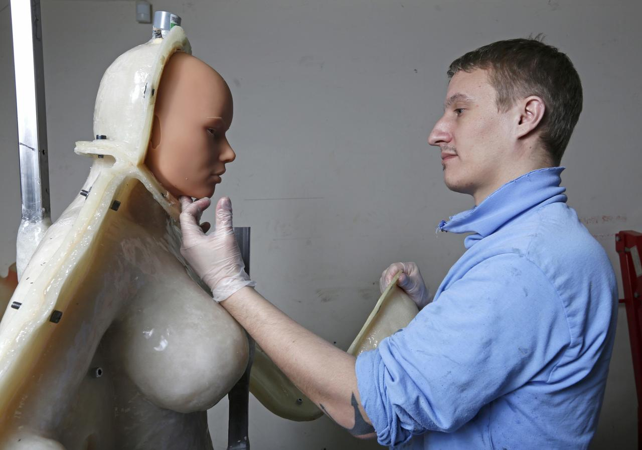 Eric, an employee at the Dreamdoll company, checks a silicone dream doll as he removes it from a mold at their workshop in Duppigheim near Strasbourg, February 18, 2015. The realistic silicone sex dolls can be ordered from a catalogue based on four hair and eye color models for a base price of 5,500 euros ($6,150). The dolls weigh around 40 kilos due to a lightweight aluminum structure and take a week to construct. The company of three employees produces some one hundred custom-made silicone sex dolls a year, mainly for European customers. Picture taken February 18, 2015.          REUTERS/Vincent Kessler (FRANCE  - Tags: SOCIETY BUSINESS)