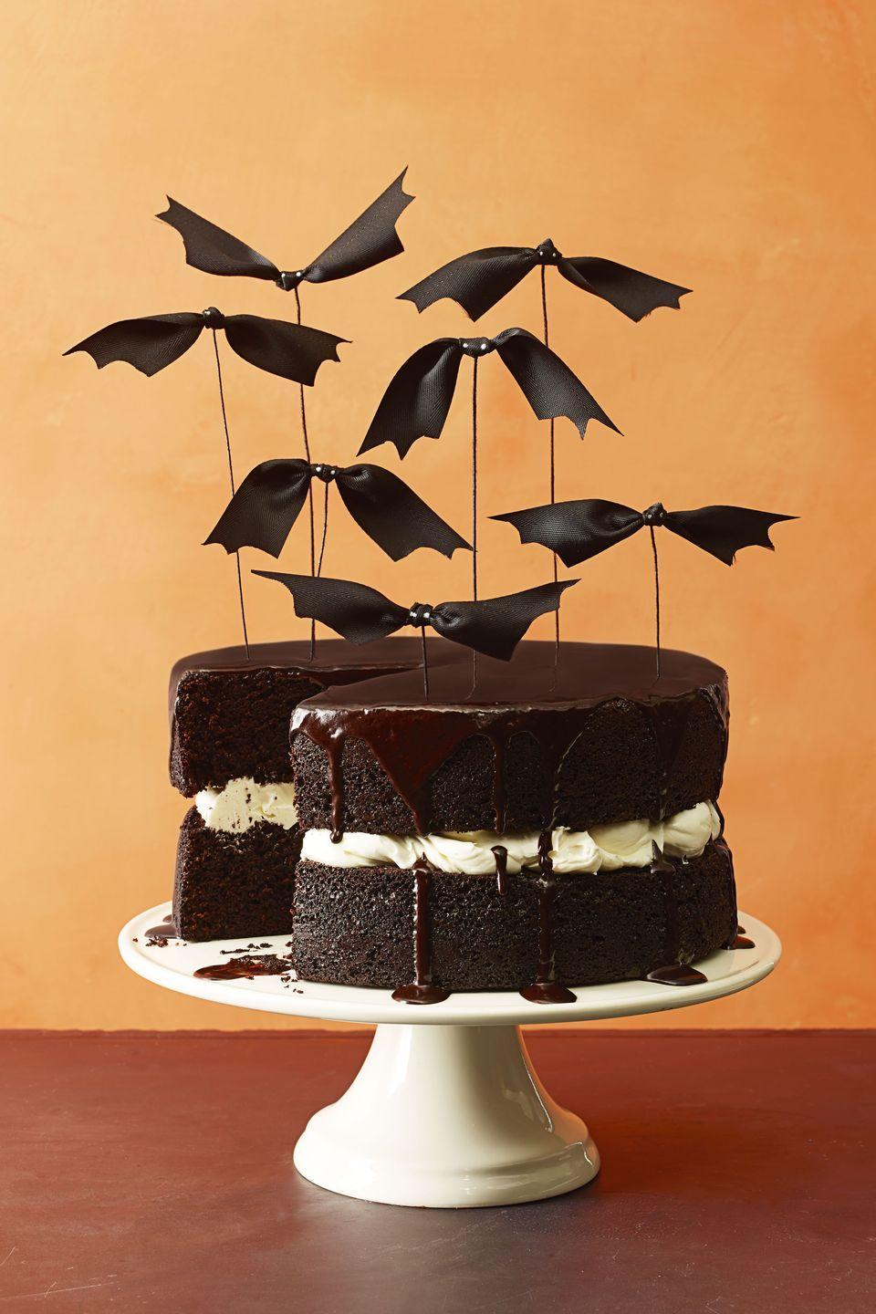 """<p>For a simple way to Halloween-ify a basic layer cake, use festive bat toppers (these can be easily made with ribbon and wire!).</p><p><em><a href=""""https://www.goodhousekeeping.com/food-recipes/a16014/chocolate-pumpkin-cake-recipe-ghk1014/"""" rel=""""nofollow noopener"""" target=""""_blank"""" data-ylk=""""slk:Get the recipe for Chocolate Pumpkin Cake »"""" class=""""link rapid-noclick-resp"""">Get the recipe for Chocolate Pumpkin Cake »</a></em></p>"""