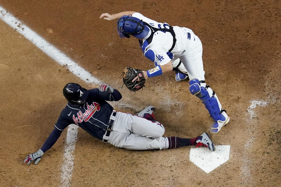 FILE - Atlanta Braves' Nick Markakis scores past Los Angeles Dodgers catcher Will Smith on a double by Cristian Pache during the fifth inning in Game 2 of a baseball National League Championship Series in Arlington, Texas, in this Tuesday, Oct. 13, 2020, file photo. Markakis has retired after a 15-year career spent with the Atlanta Braves and Baltimore Orioles. The 37-year-old Markakis, who was a free agent, told The Athletic in a story published Friday, March 12, 2021, that he was done playing after accumulating 2,388 hits, earning his lone All-Star bid in 2018 and coming within one win of reaching the World Series in his final season. (AP Photo/David J. Phillip, File)