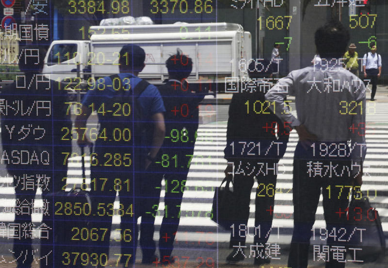People are reflected on the electronic board of a securities firm in Tokyo, Monday, May 20, 2019. Shares are mixed in Asia, with India and Australia leading gains following elections that look set to keep incumbents in office. (AP Photo/Koji Sasahara)