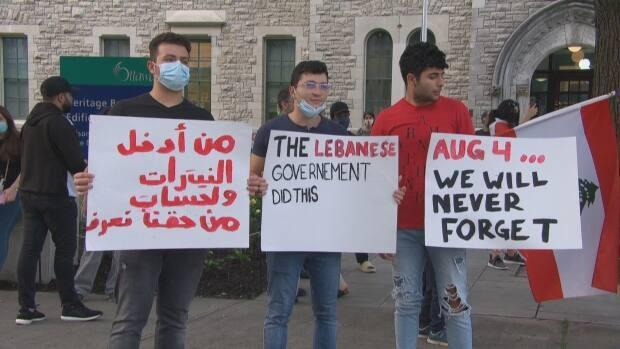 Three people hold signs calling for accountability from the Lebanese government for the Aug. 4, 2020 Beirut blast and saying they will never forget the victims of the port explosion. (Olivier Periard/Radio-Canada - image credit)