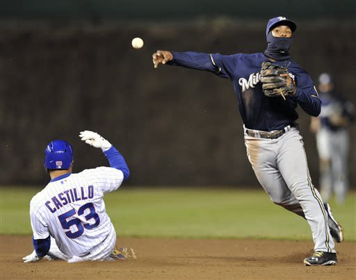 Chicago Cubs' Welington Castillo (53) is forced out at second as Milwaukee Brewers' Jean Segura throws to first on a ball hit by Luis Valbuena, who was safe during the fourth inning of a baseball game Tuesday, April 9, 2013, in Chicago. (AP Photo/Jim Prisching)
