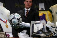 "Kendall Capps holds a soccer ball autographed by late soccer star Diego Armando Maradona ahead of the upcoming ""Sports: Legends"" auction in Culver City"