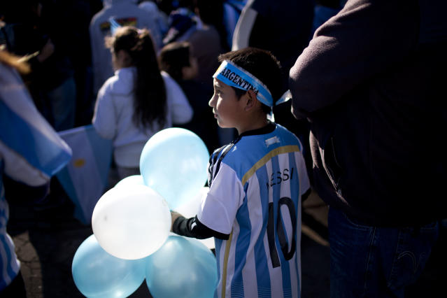 A fan of Argentina's national soccer team waits to say bye to the bus taking the players to the airport in Buenos Aires, Argentina, Monday, June 9, 2014. Argentina's team is leaving Monday to compete in the Brazil's 2014 soccer Word Cup. (AP Photo/Natacha Pisarenko)