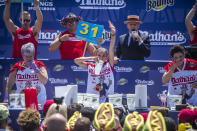 Michelle Lesco, center, competes in the 10-minute all-you-can-eat contest at the Nathan's Famous Fourth of July International Hot Dog-Eating Contest in Coney Island's Maimonides Park on Sunday, July 4, 2021, in New York. (AP Photo/Brittainy Newman)