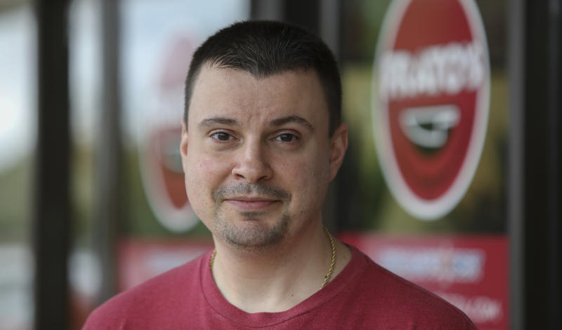 Owner Michael Kudrna poses in front of Frato's Pizza in Schaumburg, Ill., on Sept. 6, 2019. Frato's looks like a typical restaurant, but in the kitchen, cooks are whipping up dishes for four other restaurants at the same time. Kudrna launched the four spinoffs earlier this year in a matter of weeks as he races to keep his Chicago-area business ahead of a growing trend: restaurants conceived only for delivery or take-out.  (AP Photo/Teresa Crawford)