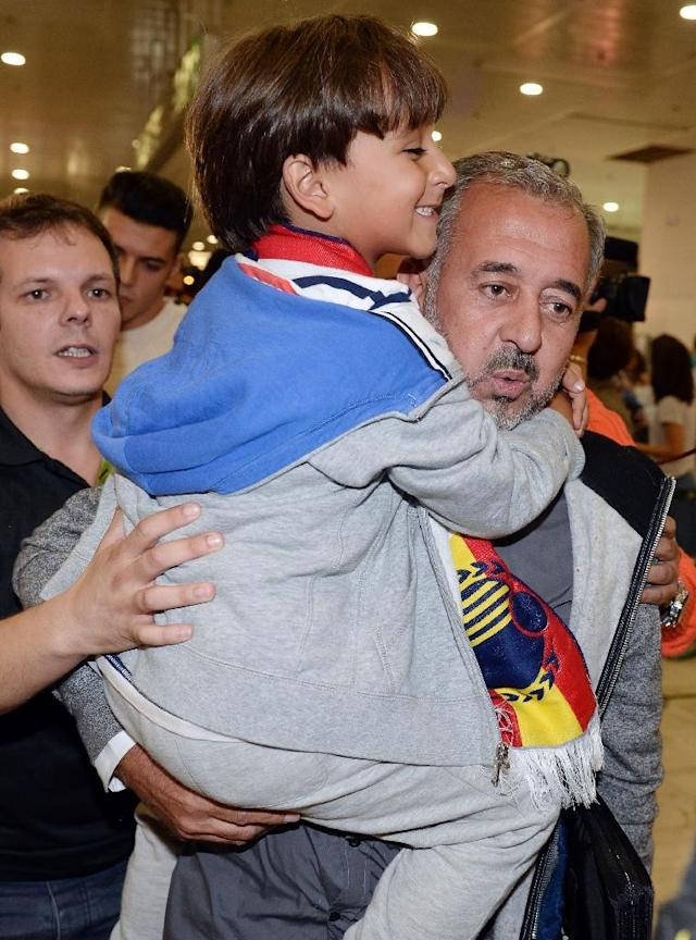 Osama Abdul Mohsen (R), the Syrian refugee who made world headlines when a Hungarian journalist tripped him over as he fled, and his son Zaid arrive in Barcelona, on September 16, 2015, prior to leaving again for Madrid (AFP Photo/Josep Lago)
