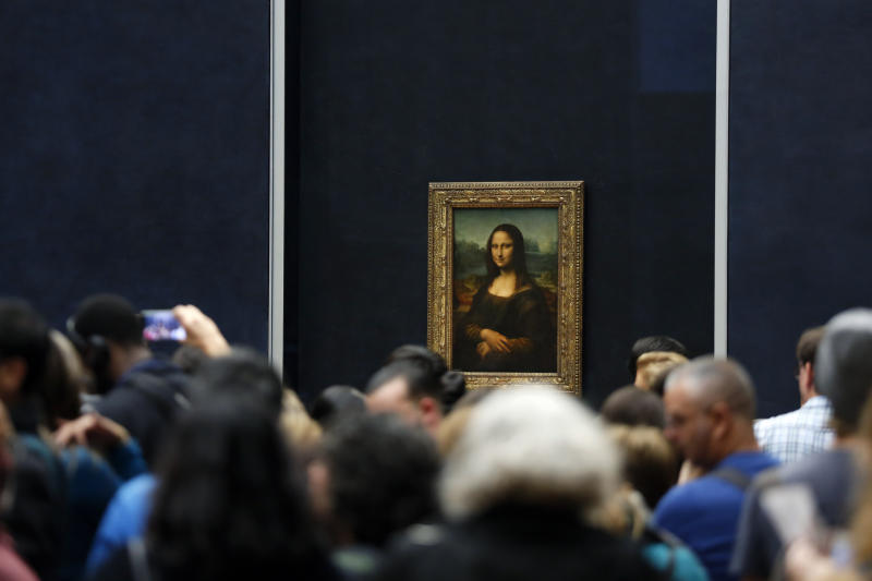 FILE - In this Oct.23, 2019 file photo, tourists wait to see Leonardo da Vinci's painting Mona Lisa, at the Louvre museum, in Paris. Iconic sites that are among some of France's biggest tourist draws won't reopen when the country lifts most of its coronavirus restrictions next week. Neither the Louvre Museum, the Eiffel Tower nor the Versailles Palace will be reopening next week when France lifts many of its remaining coronavirus lockdown restrictions. (AP Photo/Thibault Camus, File)