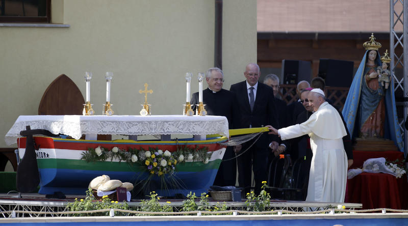 Pope Francis touches the altar made with a boat used by migrants during his visit to the island of Lampedusa, southern Italy, Monday July 8, 2013. Pope Francis traveled Monday to the tiny Sicilian island of Lampedusa to pray for migrants lost at sea, going to the farthest reaches of Italy to throw a wreath of flowers into the sea and celebrate Mass as yet another boatload of Eritrean migrants came ashore. (AP Photo/Gregorio Borgia)