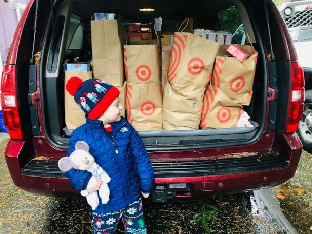 PHOTO: Hudson Galligan stands in front of a car filled with shopping bags of hot cocoa.  (Lacey Galligan)