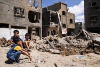 Children gather beside the crater where the home of Ramez al-Masri was destroyed by an air-strike prior to a cease-fire reached after an 11-day war between Gaza's Hamas rulers and Israel, Sunday, May 23, 2021, in Beit Hanoun, the northern Gaza Strip. (AP Photo/John Minchillo)