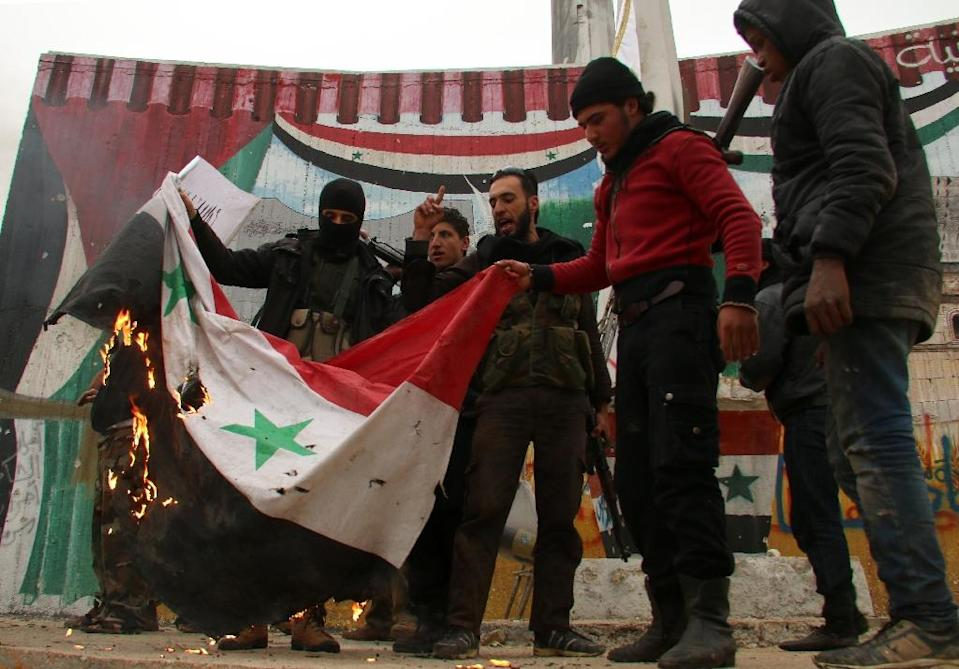 Fighters from a coalition of Islamist forces torch a Syrian flag after capturing the Syrian city of Idlib, on March 29, 2015 (AFP Photo/Zein al-Rifai)