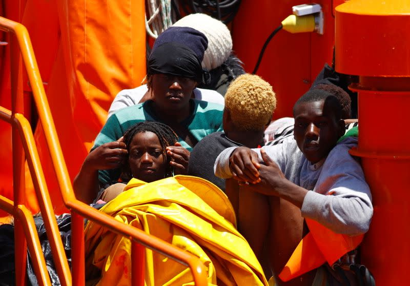 Migrants wait to disembark from a Spanish coast guard vessel, in the port of Arguineguin