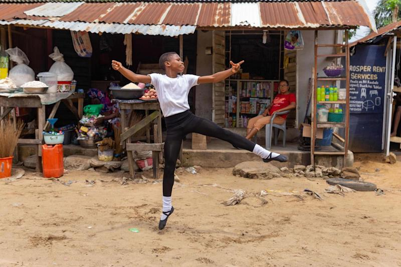 Anthony Madu performs a ballet dance routine in front of his mother's shop in Okelola street in Ajangbadi, Lagos: AFP via Getty Images