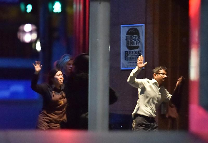 Hostages run out of a cafe in the central business district of Sydney on December 16, 2014 (AFP Photo/Peter Parks)