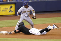 Miami Marlins' Miguel Rojas, bottom, slides past Milwaukee Brewers third baseman Pablo Reyes (33) as he is safe on a single hit by Garrett Cooper during the third inning of a baseball game, Friday, May 7, 2021, in Miami. (AP Photo/Lynne Sladky)