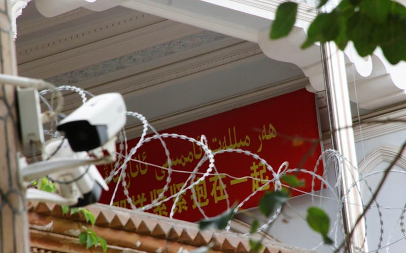 A propaganda banner and a security camera are placed on the walls of a mosque in the Old City in Kashgar - REUTERS