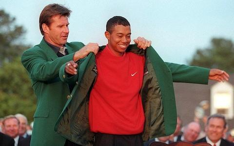 <span>Woods is given the green jacket back in 1997 after winning his first Masters </span> <span>Credit: AFP </span>