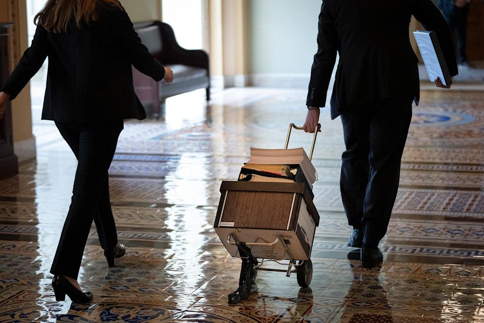 Documents, including text of the bipartisan infrastructure legislation, is wheeled toward the office of Senate Majority Leader Chuck Schumer at the Capitol in Washington, D.C, on Aug. 2, 2021.