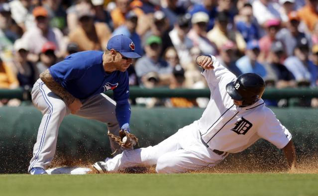 Toronto Blue Jays third baseman Brett Lawrie tags out Detroit Tigers runner Ben Guez, right, on an attempted steal during the third inning of a spring exhibition baseball game in Lakeland, Fla., Tuesday, March 18, 2014. (AP Photo/Carlos Osorio)