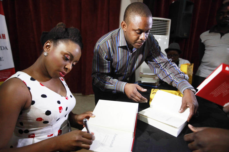 """In this photo taken, Saturday, April 27, 2013, Chimamanda Ngozi Adichie, left, signs autographs during a book launch of her new book 'Americanah', in Lagos, Nigeria. Modern life in Lagos, Nigeria's largest city, has become almost a character itself in novelist Chimamanda Ngozi Adichie's new book, """"Americanah."""" Within its pages, one catches self-acknowledged glimpses of the writer herself, who shot to fame with her previous novel, a love story set during Nigeria's civil war entitled """"Half of a Yellow Sun."""" (AP Photo/Sunday Alamba)"""