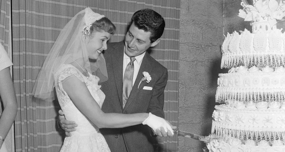Debbie Reynolds and Eddie Fisher cut the wedding cake following their nuptials in 1955 in the Catskills. Their 15-month romance was climaxed by a three-minute civil ceremony. (Photo: Getty Images)
