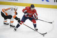 Philadelphia Flyers defenseman Travis Sanheim (6) reaches for the puck in front of Washington Capitals defenseman Dmitry Orlov (9) during the first period of an NHL hockey game Tuesday, April 13, 2021, in Washington. (AP Photo/Nick Wass)