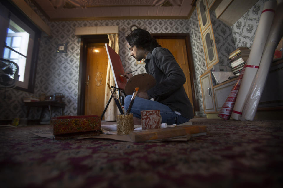 """Kashmiri artist Tabish Haider paints inside his house in Srinagar, Indian controlled Kashmir, July 22, 2020. A year after India ended disputed Kashmir's semi-autonomous status and downgraded it to a federally governed territory, authorities have begun issuing residency and land ownership rights to outsiders for the first time in almost a century. Many Kashmiris like Haider view the move as the beginning of settler colonialism aimed at engineering a demographic change in India's only Muslim-majority region. """"They have recently introduced a law which is a domicile law, which basically says that we as Kashmiris, who have been living here for past many generations, they have to prove their own identity in their own land. So how can a piece of paper prove my identity in my own land? Haider asked. (AP Photo/Mukhtar Khan)"""