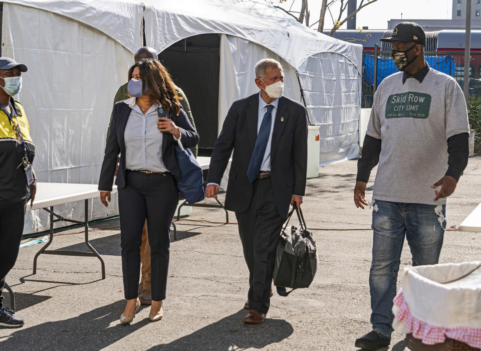 FILE - In this Feb. 4, 2021, file photo, Jeff Page, right, also known as General Jeff, a homelessness activist and leader in the Downtown Los Angeles Skid Row Neighborhood Council, walks with U.S. District Court Judge David O. Carter, middle, and Michele Martinez, special master on the issues of homelessness, after a court hearing at Downtown Women's Center in Los Angeles. A judge overseeing a sweeping lawsuit about homelessness in Los Angeles has ordered the city and county Tuesday, April 20, 2021, to find shelter for all unhoused residents of Skid Row within 180 days. Judge David O. Carter also ordered an audit of all funding related to the crisis of people living on the streets. (AP Photo/Damian Dovarganes, File)