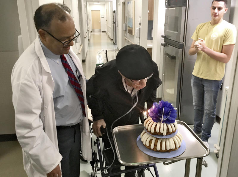 Dr. Rajneesh Nath, left, watches the Rev. John Sabbagh blow out candles on his cake for his one-year transplant anniversary as Sabbagh's grandson John, right, looks on, Friday, Sept. 7, 2018 in Gilbert, Ariz. Thirty-five years after a Mesa man cared for his son when he was shot in their native Lebanon, the son is returning that devotion. Both the Rev. John Ibraham Sabbagh and his 54-year-old son, Ebby Sabbagh, are celebrating one year of going strong since the elder Sabbagh received a crucial stem-cell transplant. (AP Photo/Terry Tang)