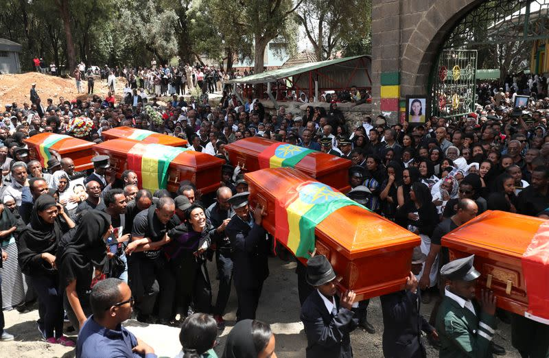 Pallbearers carry the coffins of the victims of the Ethiopian Airline Flight ET 302 plane crash, during the burial ceremony at the Holy Trinity Cathedral Orthodox church in Addis Ababa