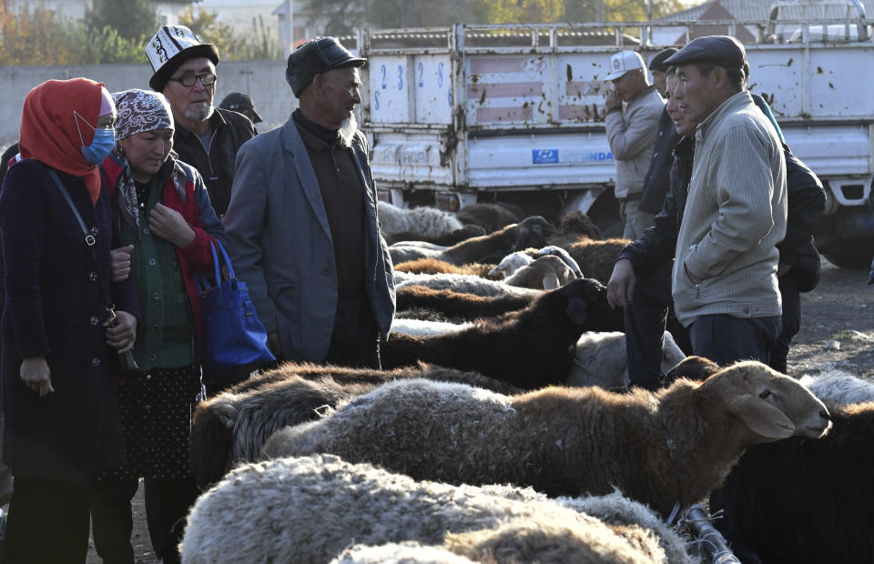 Sellers and buyers of sheeps talk to each other at the Moscow market in Belovodskoye village, about 45 kilometers (28 miles) southwest of Bishkek, Kyrgyzstan, Sunday, Oct. 18, 2020. Kyrgyzstan, one of the poorest countries to emerge from the former Soviet Union, where political turmoil has prompted many people to have little respect for authorities, whom they see as deeply corrupt. (AP Photo/Vladimir Voronin)